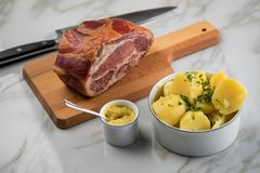 German Kassler pork neck with boiled potatoes and mustard on marble table royalty free stock image