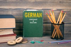 German language and culture concept. Book on a wooden background Stock Photos