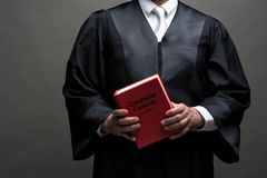 German lawyer with a robe and a book. German lawyer with a classical black robe, white tie and book stock images