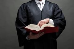 German lawyer with a robe and a book. German lawyer with a classical black robe, white tie and book royalty free stock photos