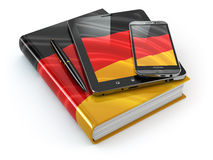 German learning. Mobile devices, smartphone, tablet pc and book Stock Photography