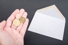 German letter postage. Hand holding 62 eurocents, which is the german letter postage in 2015, infront of an open envelope - focus is on the coins Stock Images