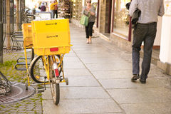 German mailman's bike. German mail bike with two Deutsche Post boxes on a street with people and lots of copy space Stock Photo