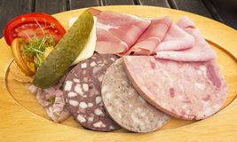 German meat cold cuts. Delicious German cold cuts of meat and sausage on a platter with tomato cress and pickle garnish Royalty Free Stock Images