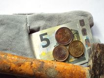 German Minimum wage 8.50. The German minimum wage as 5 euro note and coins, ying on a work glove Royalty Free Stock Photo