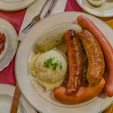 German mixed sausages for beer with mashed potatoes, greens, stewed cabbage and seasonings stock photo