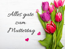 German Mother`s day card with word Muttertag. Mother`s day tulip and hearts on white wooden background stock photo