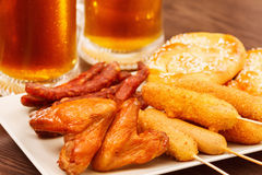 German national dishes with beer. Oktoberfest traditional food. German national dishes pretzel maishund fried wings with beer snack on wooden background royalty free stock photography