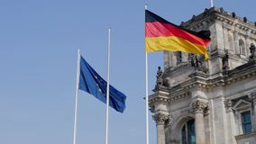 The German national flag flying in the wind together with the EU flag stock video footage