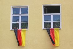 German nationalism: flags waving from two window sills. German nationalism: German flags waving from two window sills of an old yellow house royalty free stock images