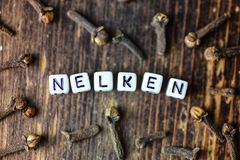 German Nelken Cloves, old wooden background, selective focus. Letter Stock Image