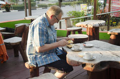 German old man eating breakfast in morning time on wooden table Stock Photos