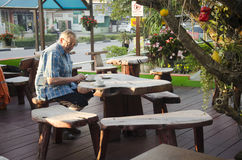 German old man eating breakfast in morning time on wooden table Stock Photo