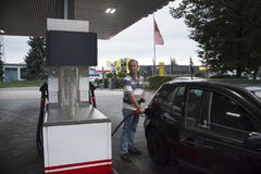 German old men people drive car go to fill oil in petrol station