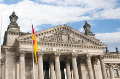 The German Parliament with the German flag in front. The Reichstag building with the text on the top, which means: To the German people Royalty Free Stock Photography
