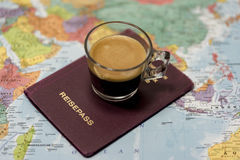 German passport and hot drink on map. Point of view perspective of German passport on top of paper color map with glass of hot beverage Stock Photos