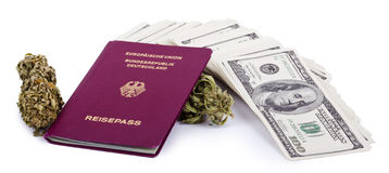 Drug Trafficking Pays Well. A German passport, two Marijuana buds and a large stack of 100 US dollar money notes  on white background Stock Photography