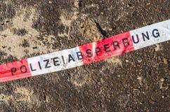 German police line red white tape on street asphalt dirt Royalty Free Stock Photos