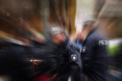 German police officers in action, focus on the POLIZEI emblem on. The uniform, blurred crowd and surrounding, background with zoom effect, copy space stock image
