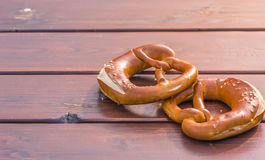 German pretzel in sunlight on table. Food photography with traditional German pretzels, on a wooden table and a beam of light in the right corner. Perfect as a Royalty Free Stock Image