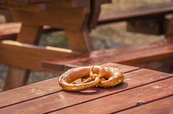 German pretzel on wooden table. Traditional german snack on wooden table, outdoor, at a rustic terrace Stock Image