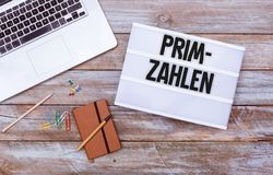 German Primzahlen prime numbers, office desk flat lay. Primzahlen German for prime numbers message in light box, grunge wood table flat lay shot from above royalty free stock photos