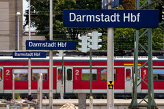 German railway station. Platform with name and train at station stock photography