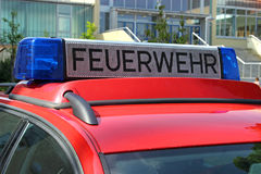 German red fire department car with blue light. German red fire brigade car with blue light in front od a school, close-up royalty free stock image