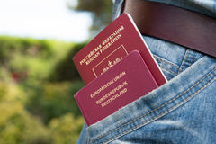 German and Russian passport in the pocket. Red German and Russian passport in the pocket Royalty Free Stock Photo