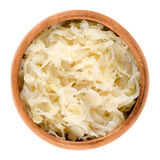 German sauerkraut in wooden bowl over white. Finely cut cabbage, fermented by lactic acid bacteria with long shelf life and distinctive sour flavor, used as a royalty free stock image