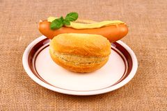 German sausage with bun, mustard and basil Royalty Free Stock Photos
