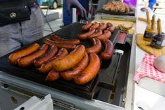German sausage on the grill sold on the street fair royalty free stock photo