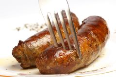 German sausages. And the fork closeup on the white plate Stock Photos