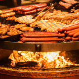 German sausages. The process of cooking over a fire. Stock Photos