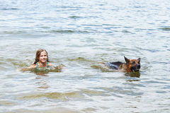 German shepherd and girl swimming in lake Stock Photos