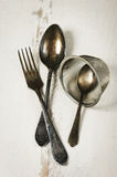 German silver spoon, fork and other utensils on a white wooden b Stock Photos