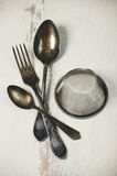 German silver spoon, fork and other utensils on a white wooden b Royalty Free Stock Images