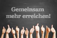 German slogan on chalkboard. German slogan 'Gemeinsam mehr erreichen' (Together we achieve more) on chalkboard Stock Photo