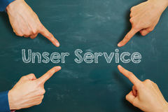 German slogan. Hands pointing to German slogan Unser Service (our service) on a chalkboard Royalty Free Stock Image