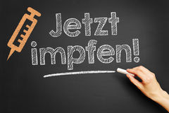 German slogan. `Jetzt impfen` vaccinate now written with chalk on blackboard Royalty Free Stock Images