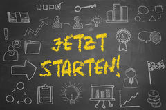German slogan. `jetzt starten!` start now! on blackboard with many business icons Stock Photography