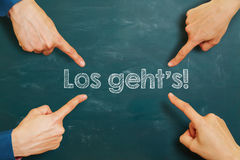 German slogan. `Los geht`s` let`s go on a chalkboard with hands pointing at it Stock Photography