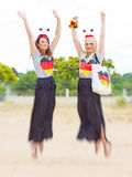 German soccer fan. Girls with german fan outfit jumping in the air Royalty Free Stock Image