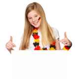 German soccer fan showing on copyspace. German fan pointing on a white placard with blank space for text Royalty Free Stock Image