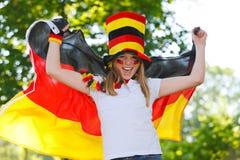German soccer fan waving her flag. German soccer fan waving a flag outdoor royalty free stock photo