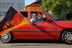 German soccer fans celebrating another victory. A German soccer fan showing the victory sign and swinging his large flag in a red car during a motorcade royalty free stock image