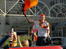 German soccer fans celebrating another victory. A German soccer fan cheering enthusiastically and swinging his flag in a red ragtop during a motorcade. world royalty free stock photography