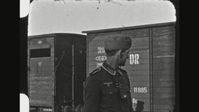 German Soldier With Daughter Posing Upon Departure. GERMANY, BAVARIA, AUTUMN 1941.German Soldier Posing With Daughter In Front Of A Deutsche Reichsbahn Freight stock video footage