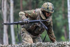 German soldier with hk g 36 rifle on assault course. BURG / GERMANY - JUNE 25, 2016: german soldier with hk g 36 rifle on assault course , at open day in barrack Stock Photos