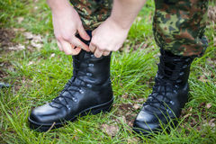 German soldier laces his boots on grass Royalty Free Stock Photography